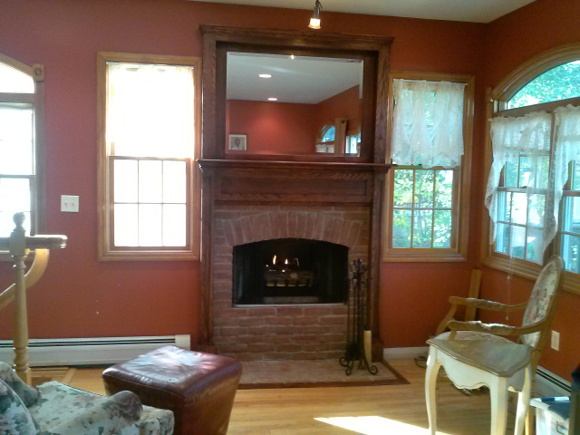 Woodburning fireplace with hidden personality...custom hanging screens, custom old brick arched firebox surround with hearth extention, beveled mirrored oak overmantel, mantel with hearth moulding all in hand rubbed red mahogany finish.